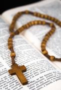 Bible with rosaries-beads crucifix - stock photo
