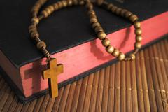 Bible with rosaries-beads crucifix on a straw table - stock photo