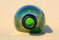 Green bottle on the sand Stock Photos
