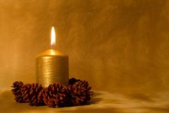 christmas candle burning in golden light with pine cones - stock photo