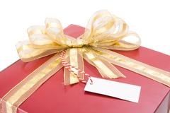 Red gift with a golden bow and tag isolated on white background. Stock Photos