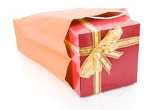 Red gift with a golden bow inside a shopping bag isolated on white background. Stock Photos