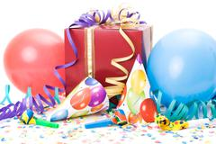 Stock Photo of gift, party hats, horns or whistles, confettis and balloons on white background.