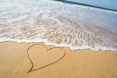 heart drawn in the smooth beach sand - stock photo