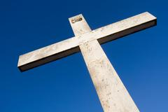 large stone cross against clear blue sky - stock photo