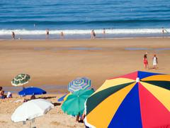 crowded beach at summer with sun umbrellas. - stock photo
