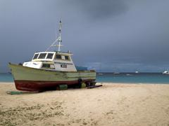 fishing boat ashore on beach - stock photo