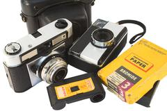 old, vintage film cameras with photo paper, negative roll and case. - stock photo