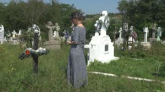 Woman bringing candle in cemetery cross lady ritual at grave tomb commemorate Stock Footage
