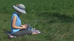 Businesswoman working on laptop on the grass, garden, summer, grass, holiday Stock Footage