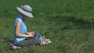 Businesswoman working on laptop on the grass, garden, summer, grass, holiday Stock Footage