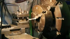 Industrial worker makes a stud using a lathe machine - stock footage