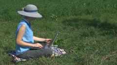 Businesswoman working on laptop on the grass, holiday, relax, business, young  Stock Footage