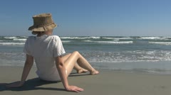 Woman relaxing on the beach  sunlight hat leisure bathe ripple hat marine resort Stock Footage