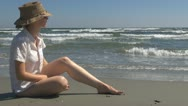 Young woman relaxing on the beach, sitting, nature, holiday, ocean, sea sand Stock Footage