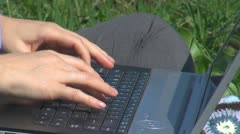 Business woman working on laptop on the grass close-up of fingher tape in garden Stock Footage