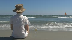 Beautiful woman drinking white wine on the beach lifestyle champagne hat lady  Stock Footage