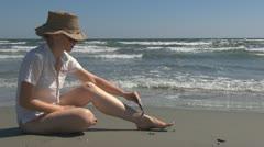 Woman shaving her legs on the beach freshness girl hygiene ocean spa sea day Stock Footage