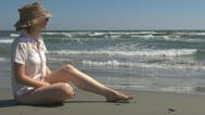 Young woman relaxing on the beach, hat ocean, sea, girl, lifestyle, holiday wave Stock Footage