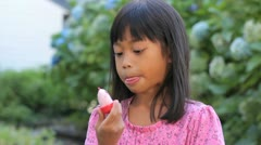 Cute Asian Girl Licking Her Popsicle Stock Footage