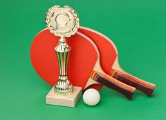 Sports awards and  tennis racquets on  green table Stock Photos