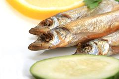 smoked fishes with lemon, cucumber and green parsley. - stock photo