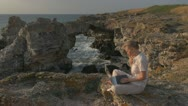 Young woman working on laptop beach coast rock lifestyle business play chatting  Stock Footage