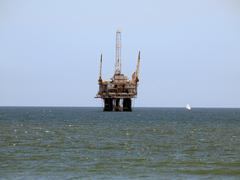 Oil rig and sail boat Stock Photos