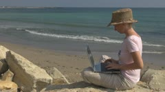 Businesswoman working on laptop on the beach coastline business holiday connect Stock Footage