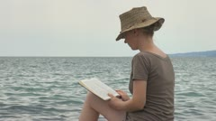 Woman read on the beach rock coastline stone sea ocean exotic lifestyle girl  Stock Footage