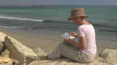 Woman reading drinking white wine on the beach ocean rock wave lifestyle hat sea Stock Footage