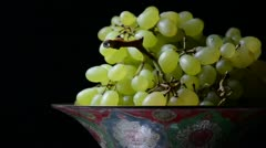 White grapes on an old painted bowl on a black background. (Rotating) Stock Footage