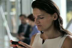 Young businesswoman with smartphone in the office hall Stock Footage