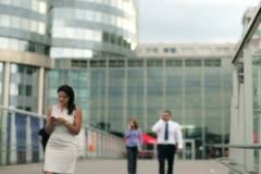 Businesspeople talking on mobile phone in front of skyscrapers - stock footage