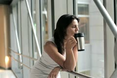 Young businesswoman resting in the office hall during coffee break Stock Footage