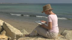 Beautiful woman reading and drinking white wine on the beach nature natural life Stock Footage