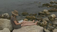 Beautiful girl reading on the beach book learn agenda consultation lifestyle  - stock footage