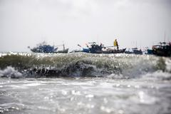 Wave and fisher boats on the coastline and beautiful beach of Vietnam. Stock Photos