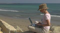 Business woman working on laptop beach, coast rock ocean sea gulf succes girl  - stock footage