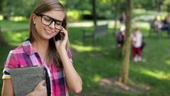 Female student talking on cellphone in the park, steadicam shot HD - stock footage
