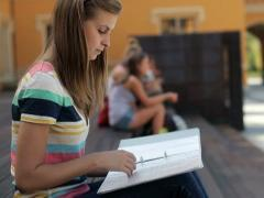 Young female student reading notes in the city, steadicam shot NTSC Stock Footage