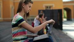 Young student with laptop relaxing in the city, steadicam shot HD - stock footage