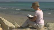 Woman reading on the beach, coastline tropical enjoy relax ocean book sitting  Stock Footage