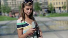 Young female student with smartphone in the city, steadicam shot HD Stock Footage