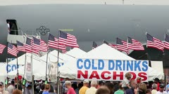 Nachos and cold drinks vendors sign with flags and crowd Stock Footage