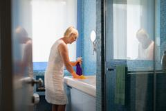 Active retired woman doing chores and cleaning bathroom at home Stock Photos