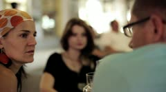 Three friends in restaurant drinking beer in the evening, steadycam shot Stock Footage