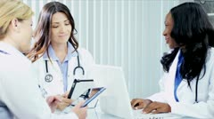 Multi ethnic female doctors in white coats using tablet Stock Footage
