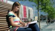 Stock Video Footage of Young female student doing homework in the city, steadicam shot HD