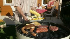 Seniors putting meat and vegetables on kettle barbecue Stock Footage